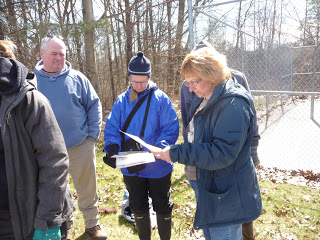 From left to right, John, Kim and Laura examine benthic invertebrate ID sheets.