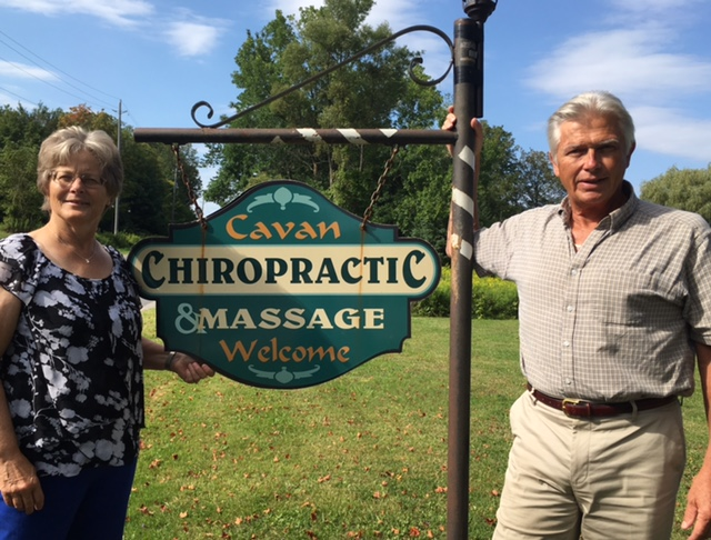 Photo of Lynn and Larry Smith beside their Cavan Chiropractic sign